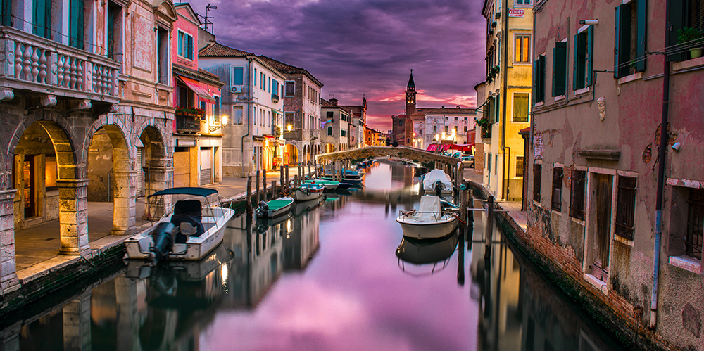 Boats along the waters of Venice, Italy with reflective violet sky on the water and buildings on each side of the river
